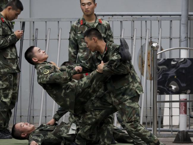 Chinese paramilitary policemen practice self-defence in Beijing. China has warned India not to underestimate its military determination amid a major stand-off over mountain territory. Picture: AP Photo/Andy Wong.Source:AP