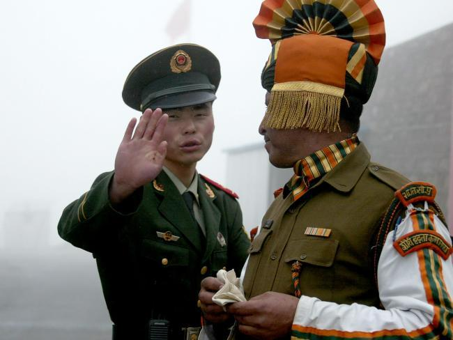 This file photo taken on July 10, 2008 shows a Chinese soldier (L) next to an Indian soldier at the Nathu La border crossing in India's northeastern Sikkim state. Picture: AFP PHOTO / DIPTENDU DUTTASource:AFP