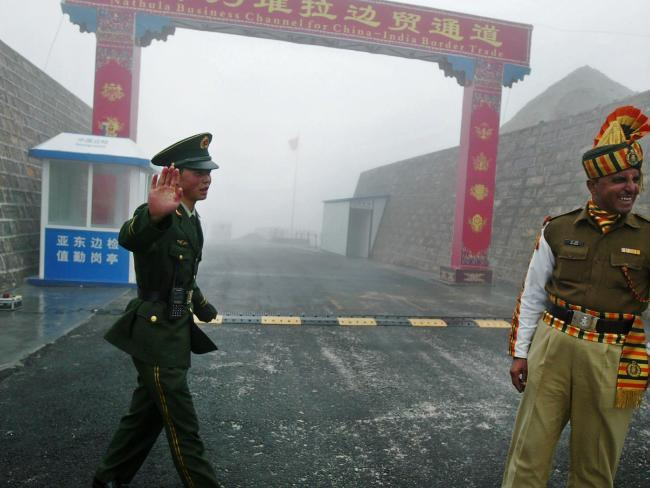 """This file photo taken on July 10, 2008 shows a Chinese soldier (L) next to an Indian soldier at the Nathu La border crossing between India and China in India's northeastern Sikkim state. China's ambassador said this month that the withdrawal of Indian troops from a disputed territory is a """"precondition"""" for peace. Picture: AFP PHOTO / DIPTENDU DUTTASource:AFP"""