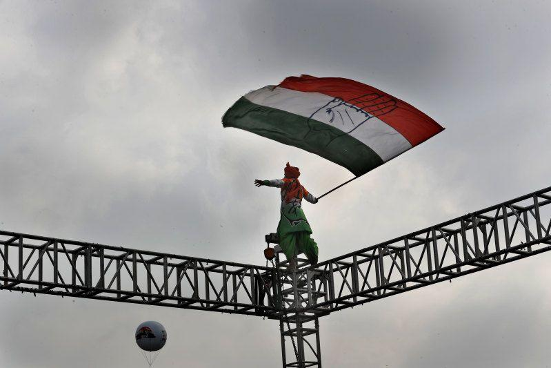 An opposition Congress party worker waves a party flag atop steel scaffolding at a rally protesting against the