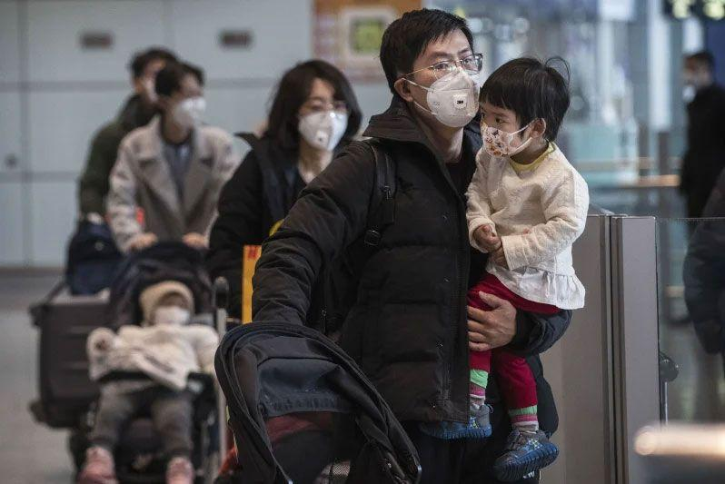 Passengers-wear-protective-masks-as-they-walk-in-the-arrivals-area-at-Beijing-Capital-Airport