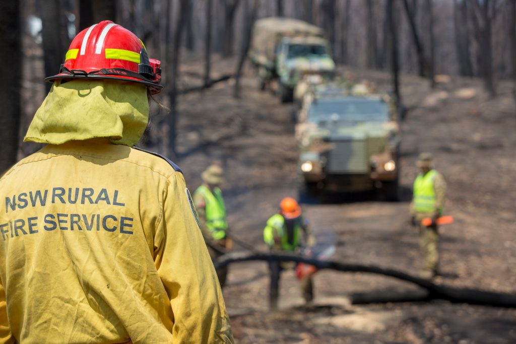A NSW Rural Fire Service member monitors conditions as Australian Army personnel clear fallen trees near Cobargo