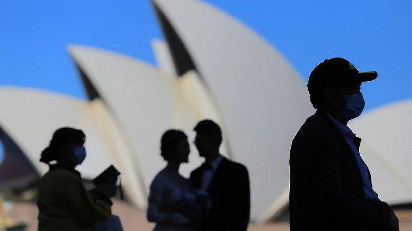 People wear face masks in front of the Sydney Opera House in Sydney.