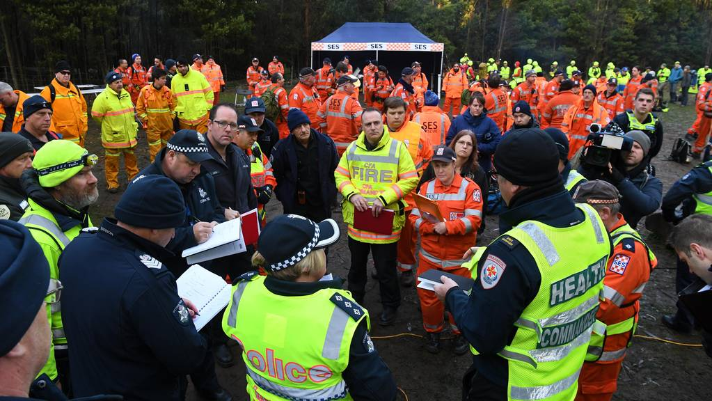 Emergency service personnel attend a briefing at the base camp at Mount Disappointment in Victoria