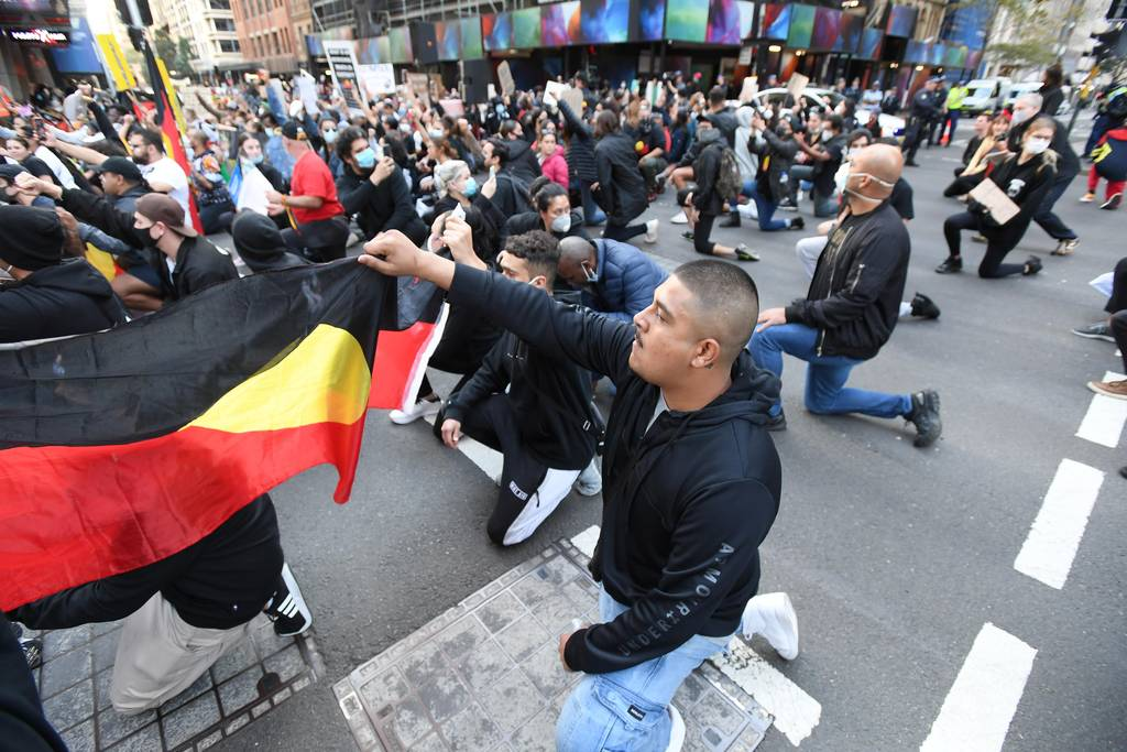 Protesters hold the Aboriginal flag during the Sydney rally