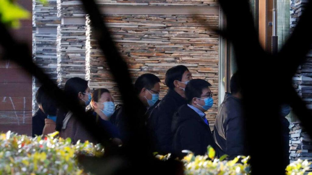 Chinese officials arrive at a hotel where WHO team stay, in Wuhan